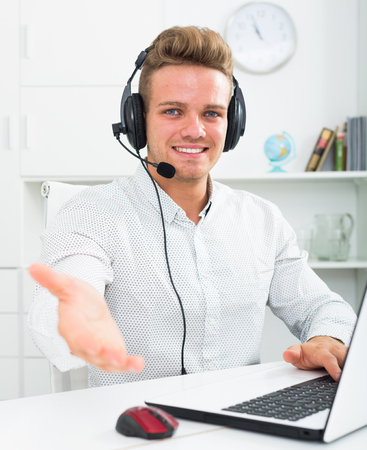 Young professional inviting to join him in call center