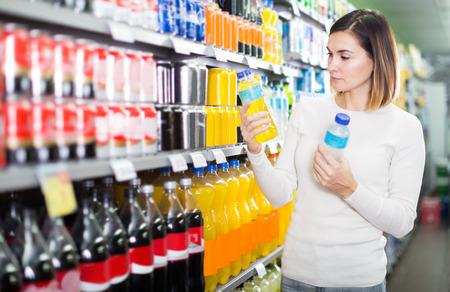 Clienta buscando bebidas refrescantes en un supermercado