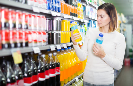 Girl customer looking for refreshing beverages in a supermarket Stock Photo - 100534349