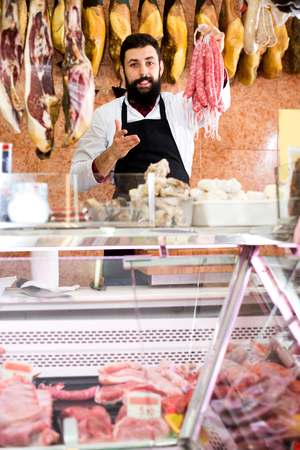 Smiling man seller showing different sausages in butcher's shop