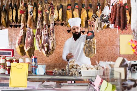 Venditore di uomo che mostra jamon in macelleria Archivio Fotografico