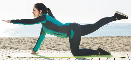 Young italian woman doing yoga poses on sunny beach by ocean