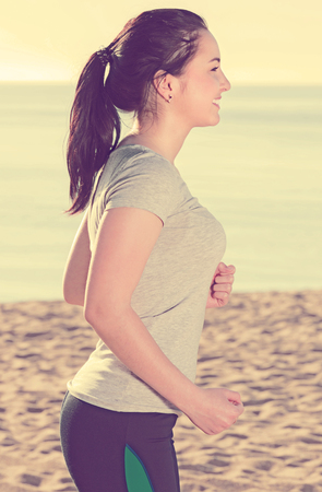 Positive girl running on beach on sunny day Stock Photo