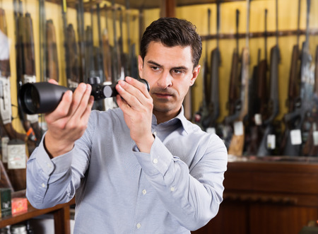 Portrait of male owner of hunting shop checking optical sights indoors