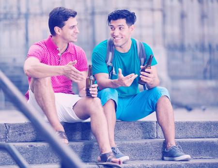 Men friends are talking and drinking beer in time walking in a city