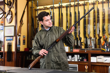 Confident cheerful positive hunter male wearing windbreaker in hunting shop with rifle in hands Фото со стока - 100531409