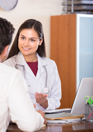 Positive doctor receiving ill adult patient at office and questioning Stock Photo