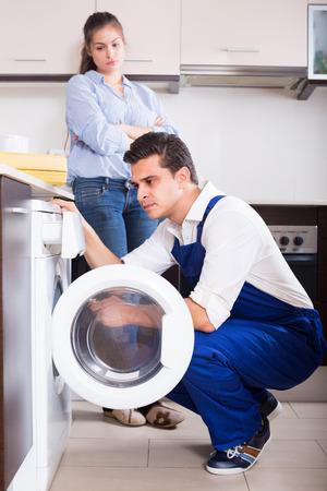 Professional mechanic repairing broken washing machine at clients kitchen Banque d'images