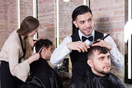 Male hairdresser cutting hair of male client with scissors in modern hair salon Archivio Fotografico