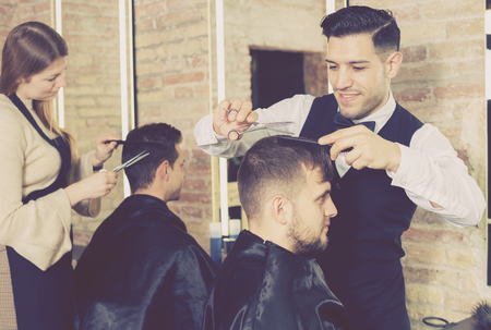 Skillful man barber making haircutting for male client in hair studio