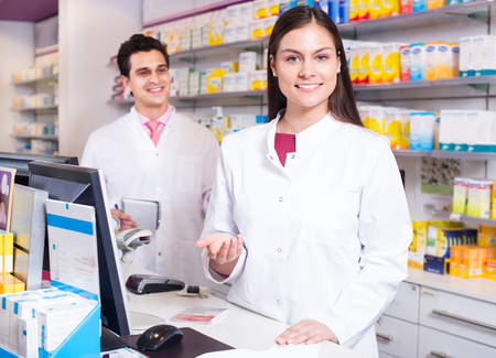 Cheerful pharmacist standing at a pay desk and pharmacy technician helping
