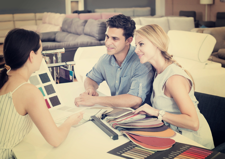 Portrait of a adult couple who are consulting with the assistent about the choice of a color for new sofa