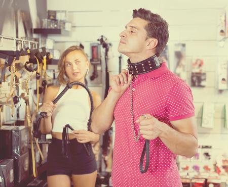 とげと革のまつげで襟を選択する買い物客のカップル
