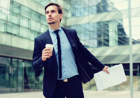 Professional man in jacket with documents hurrying to meeting