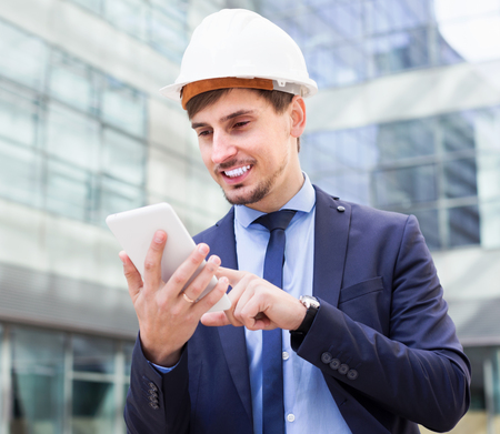 Portrait of smiling man working outdoors at modern touchpad