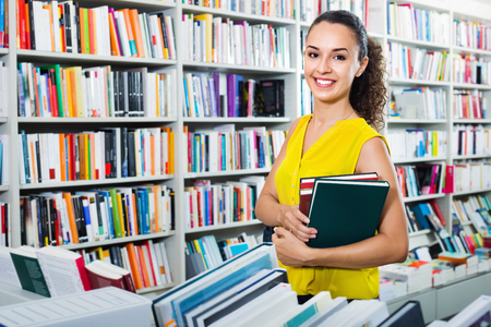 Young  positive woman buying books in hard cover in bookstore Stok Fotoğraf