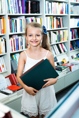 Small smiling blond  girl standing in book store and taking chosen literature