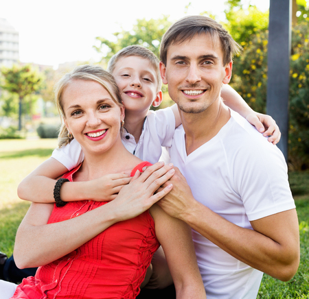 Portrait of cheerful smiling family with boy in school age happily hugging each other in park Banque d'images - 100684919