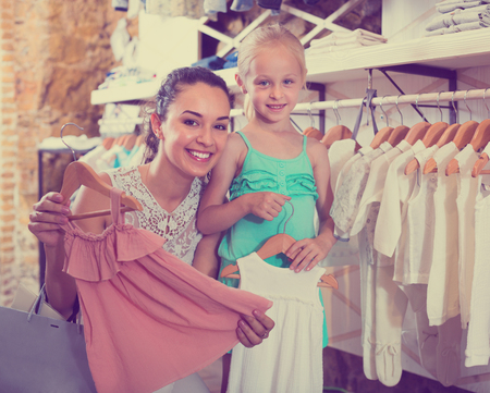 Young cheerful woman with small girl choosing white baby clothes in kids apparel boutique