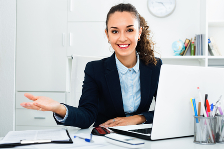 Cheerful smiling  business lady sitting at office desk with laptop