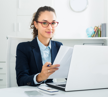 Portrait of successful businesswoman working at laptop in modern office