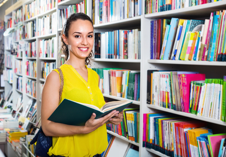 Smiling charming beautiful glad woman standing with open in publishers store Stok Fotoğraf