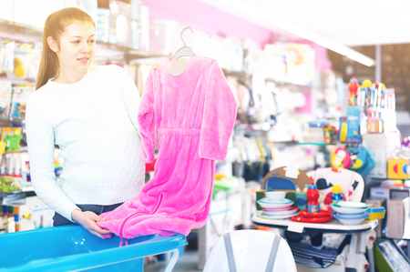 young pregnant female is buying clothes for baby in the childrens goods store Stock Photo