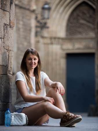 Smiling young woman sitting near old stone cathedral wall  스톡 콘텐츠