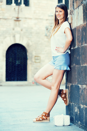 Smiling young woman resting against old stone cathedral wall  Stock Photo