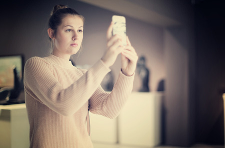 Positive female visitor using  phone  in the historical museum  Stock Photo