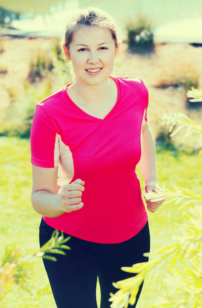 Woman in pink T-shirt is training in the park.