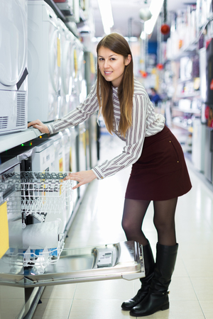 Positive girl looking for functional dish washer in shop of consumer electronics