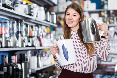 Modern female housewife buying electric kettle in kitchen appliances section