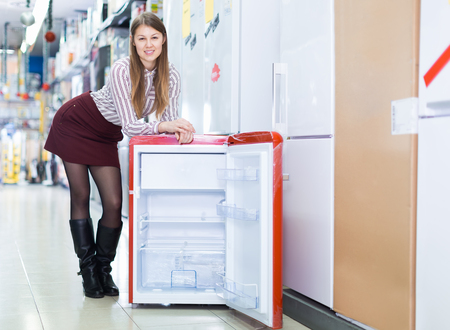 Portrait of young attractive salesgirl in store of house appliances Imagens