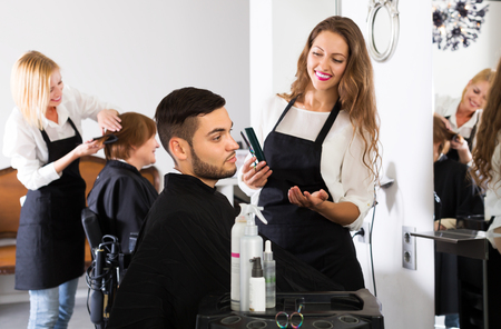 Smiling professional woman hairdresser doing hairstyle for young men Standard-Bild
