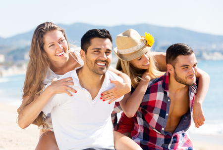 Cheerful couples hugging on beach enjoying romance and sun. Focus on the left couple