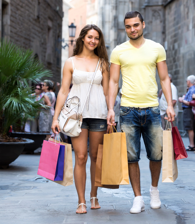 Smiling tourists hunting after souvenirs in shopping tour