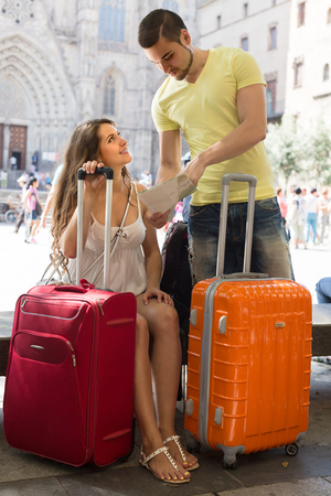 Smiling young couple with luggage and the map at street