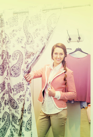 Attractive girl trying on new blouse at fitting-room in apparel store