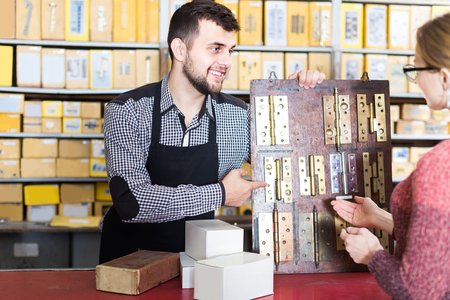 Young european seller helping female client to choose door hinges in houseware shop  Stock Photo