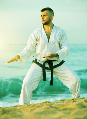 Serious young guy doing karate poses at  sunset sea shore