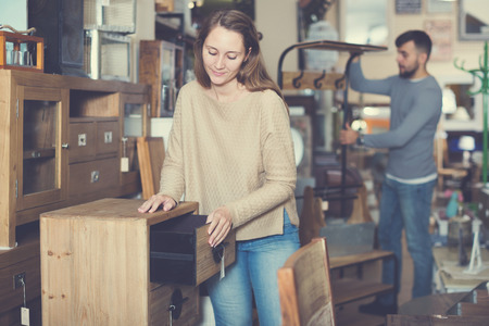 Happy young woman looking for stylish small cabinet in shop of secondhand furniture