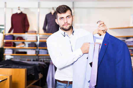 positive adult owner guy displaying jacket in fashion store