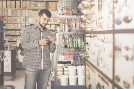 young man customer examining various glue tubes in houseware store