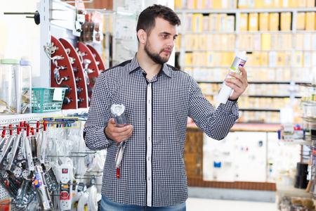 Glad adult man choosing new glue gun in houseware store Imagens