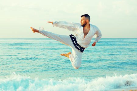 Diligent serious young man in uniform doing taekwondo exercises at  sunset sea shore Stock Photo