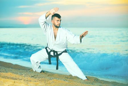 Friendly smiling  pleasant man in uniform doing taekwondo exercises at  sunset sea shore