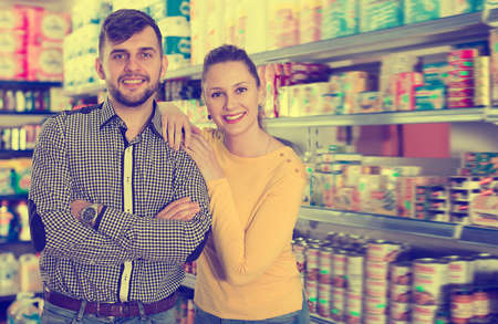 Young loving couple standing among shelves with groceries in supermarket Standard-Bild