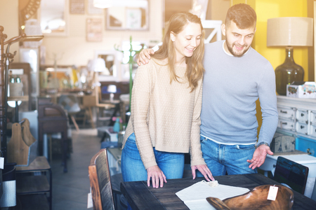 Young couple choosing vintage table for apartment in furnishings store