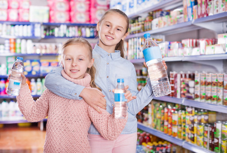 Portrait of cheerful little girls standing among shelves in the supermarket, holding the bottled water